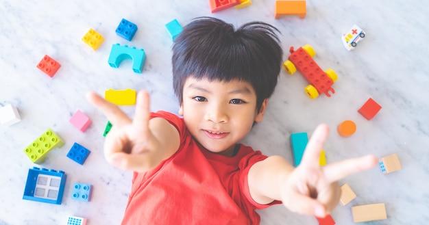 Niño feliz rodeado de coloridos bloques de juguete vista superior v forma de mano para la victoria