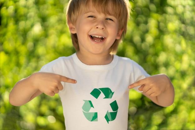Niño feliz señala con el dedo al signo de reciclaje en la camiseta. niño divertido contra la vegetación primaveral. concepto de ecología y día de la tierra.