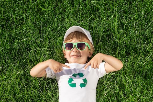 Niño feliz señala con el dedo al signo de reciclaje en la camiseta