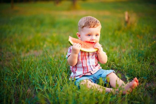 Niño feliz sentado en la hierba verde y comiendo sandía al aire libre en el parque de primavera contra natural