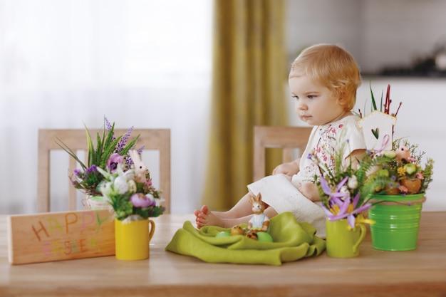 Niño feliz sentado en la mesa y sosteniendo el huevo de pascua
