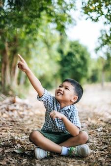 Niño feliz sentado y pensando solo en el parque