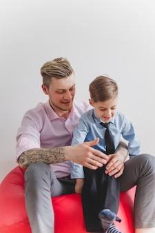 Niño feliz sentado en las piernas de su padre