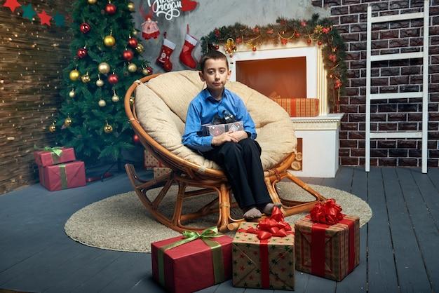 Niño feliz en una silla cómoda cerca del árbol de navidad junto a la chimenea con un montón de regalos.
