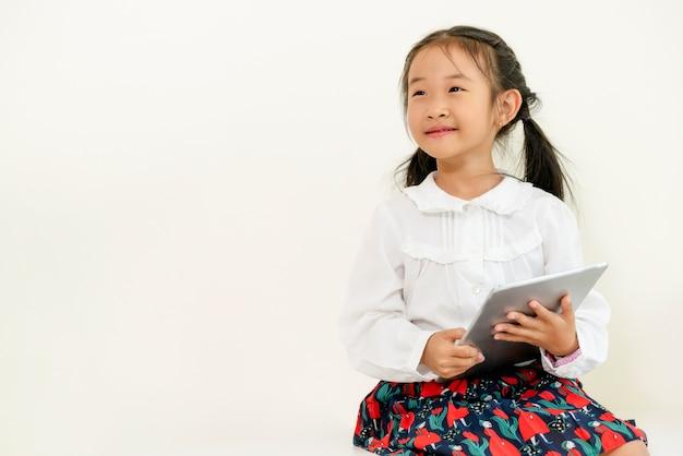 05c5e69cb Niño feliz sobre fondo blanco con tableta. estilo de vida de la infancia |  Descargar Fotos premium