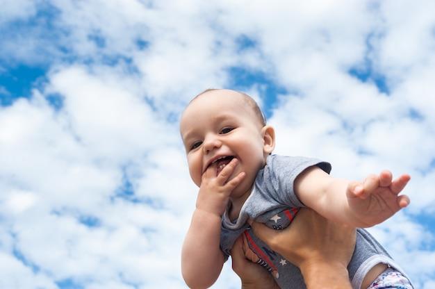 Niño feliz sobre un fondo de cielo azul y nubes