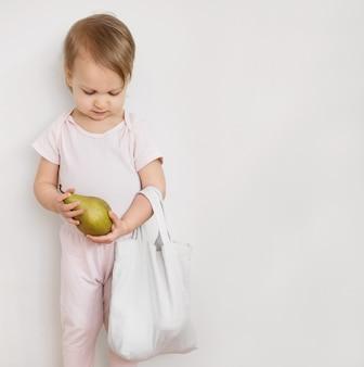 Niño feliz sostenga la fruta de pera de una bolsa textil reutilizable ecológica
