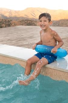 Niño feliz de tiro completo con aro salvavidas