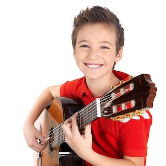 Niño feliz está tocando la guitarra acústica, aislada