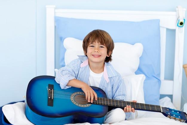 Niño feliz tocando la guitarra en la cama