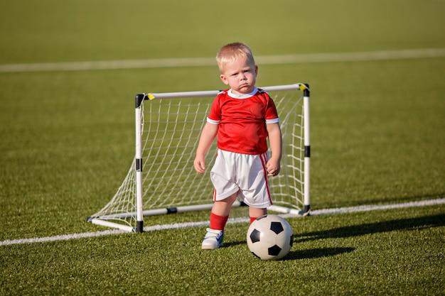 Niño feliz en uniforme deportivo jugando al fútbol con la pelota en el campo cerca de la meta