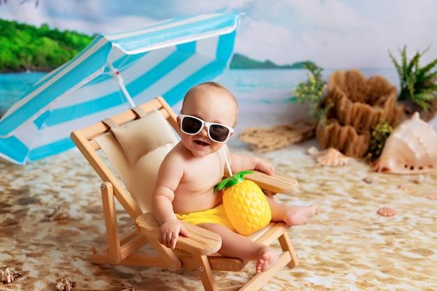 Niño feliz en vasos se encuentra en una tumbona, toma el sol en una playa de arena junto al mar y bebe jugo