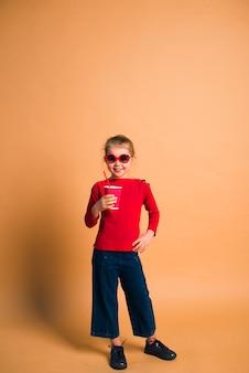 Niño feliz vistiendo moda casual jeans, suéter y gafas de sol posando con una taza de café sobre fondo de color