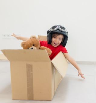 Niño feliz volando en una caja y con un sombrero con su juguete