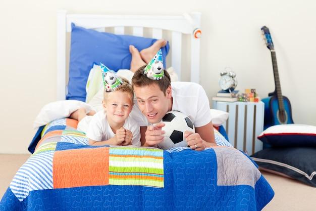 Niño feliz y su padre mirando un partido de fútbol