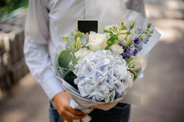 Niño con un festivo brillante ramo de flores en tonos azules