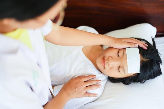 Niño con fiebre con enfermera o médico midiendo la temperatura del niño enfermo.
