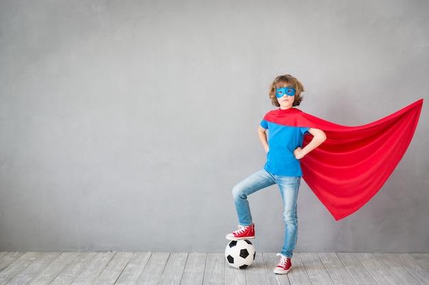 Niño finge ser superhéroe de fútbol niño jugando con pelota en casa victoria e imaginación