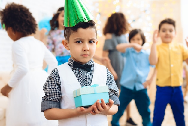 Niño frustrado con sombrero verde está de pie en la habitación en cumpleaños.