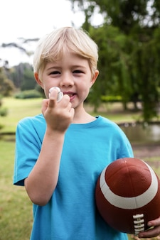 Niño con un fútbol americano usando un inhalador para el asma