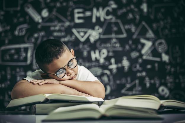 Un niño con gafas estudiando y somnoliento.