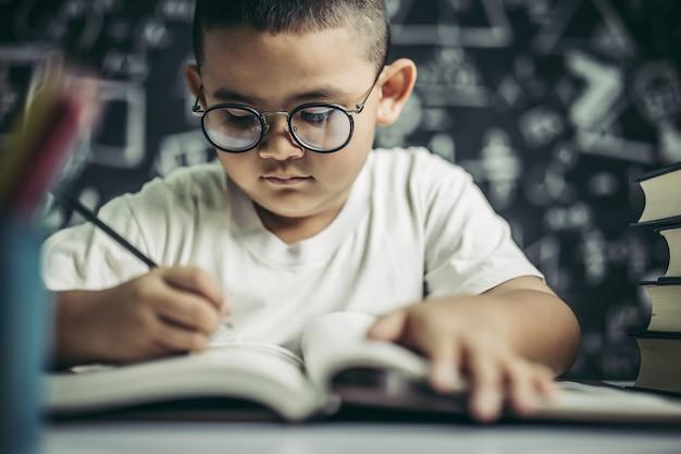 Un niño con gafas hombre escribiendo en el aula.