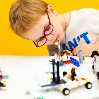 Niño con gafas jugando con bloques de juguete de construcción lego en casa