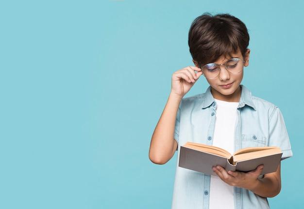 Niño con gafas leyendo tiempo