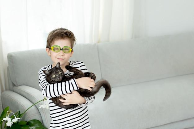 Niño con gafas de natación tiene un gato negro y sueña con nadar en verano