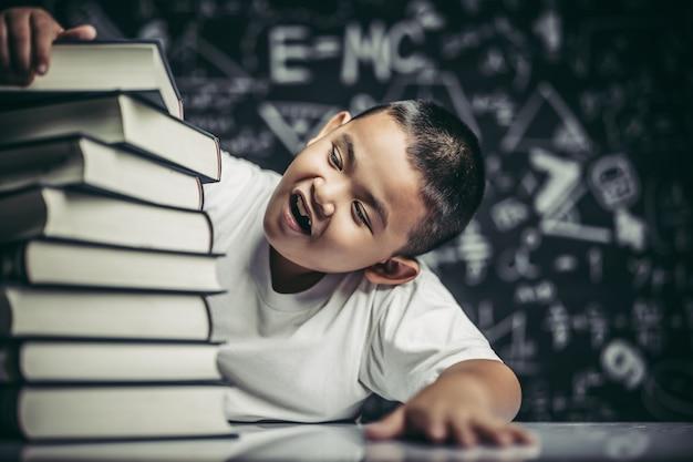 Un niño con gafas sentado en el aula contando libros.