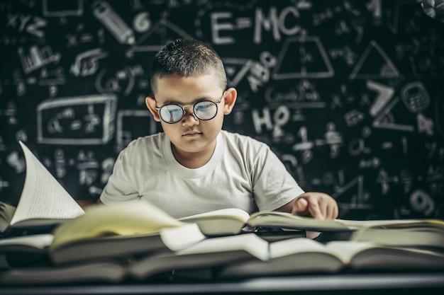 Un niño con gafas sentado en el aula leyendo.