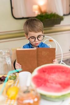 Niño con gafas de sol leyendo en la mesa