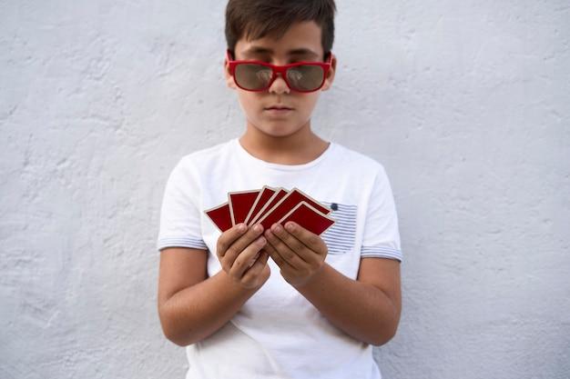 Niño con gafas de sol rojas jugando al póquer