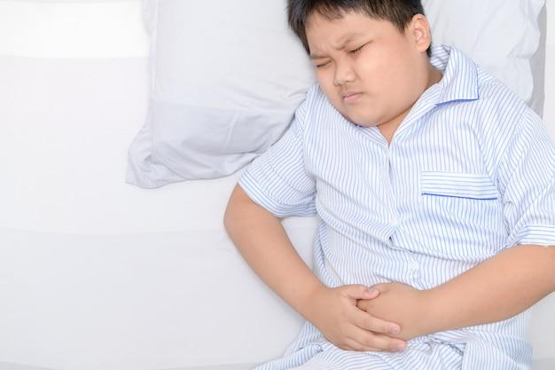 Niño gordo asiático que sufre de dolor de estómago