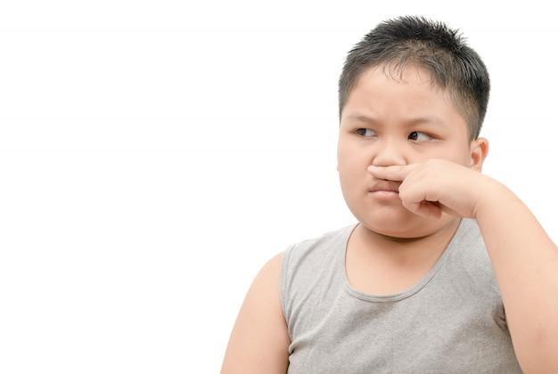 Niño gordo cubriéndose la nariz por mal olor.