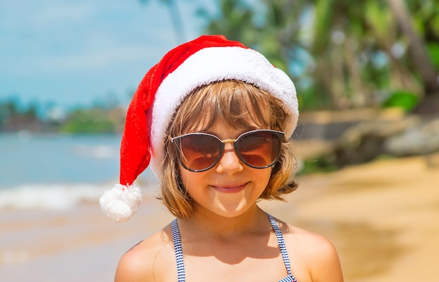 Niño con gorro de papá noel y gafas de sol en la playa.