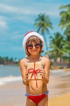 Niño con gorro de papá noel y gafas de sol con un regalo en la playa.
