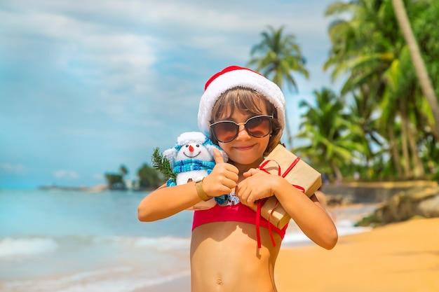 Niño con gorro de papá noel y gafas de sol con regalos en la playa.