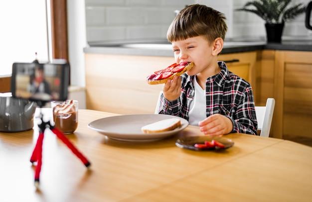 Niño grabándose a sí mismo mientras come