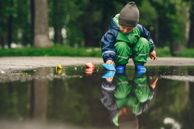 Niño gracioso en botas de lluvia jugando en un parque de lluvia