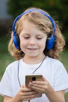 Niño gracioso con cabello largo escuchando música con teléfonos azules y un móvil