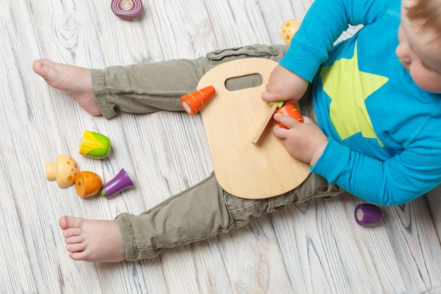 Niño gracioso juega en el chef. baby boy corta verduras de madera.