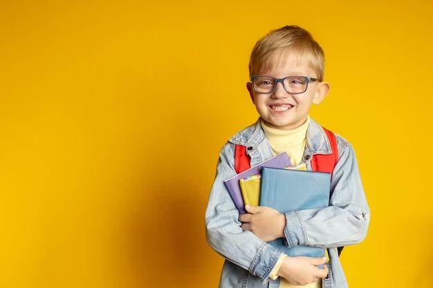 Niño gracioso niño colegial con libros sobre fondo amarillo