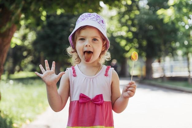Niño gracioso con paleta de caramelo, niña feliz comiendo grande