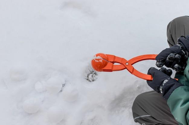 Niño en guantes de esquí tiene un dispositivo para hacer bolas de nieve. entretenimiento al aire libre en invierno. copia espacio