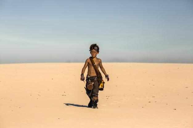 Niño guerrero post-apocalíptico al aire libre en el desierto del desierto