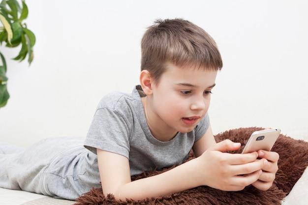 El niño habla por teléfono mientras está acostado en la cama. comunicarse con amigos y familiares en cuarentena durante el coronavirus
