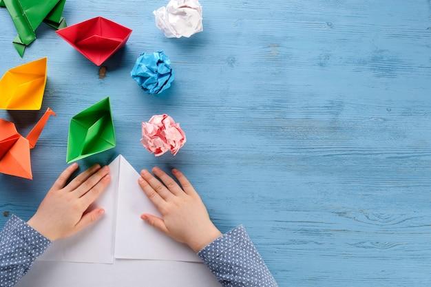 Niño hace botes de origami en una mesa azul