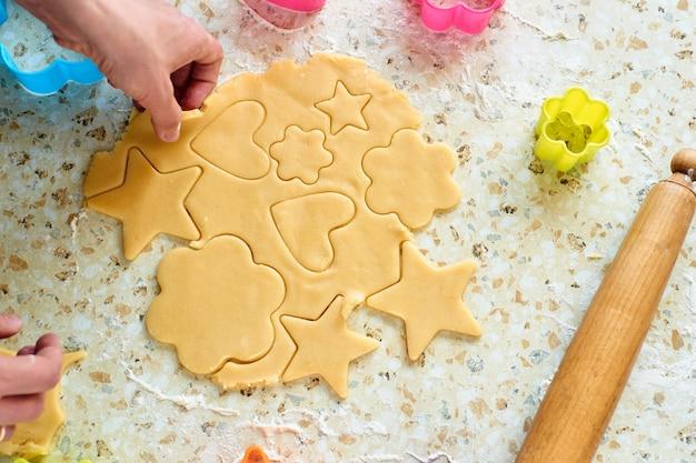 Un niño hace galletas, extiende la masa y usa formularios para hacer galletas.