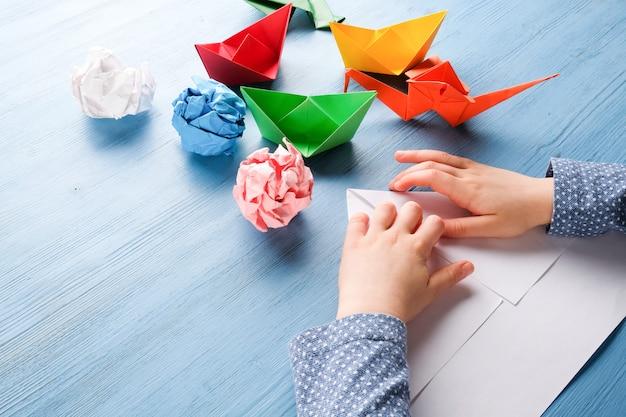 Niño hace origami en una mesa azul